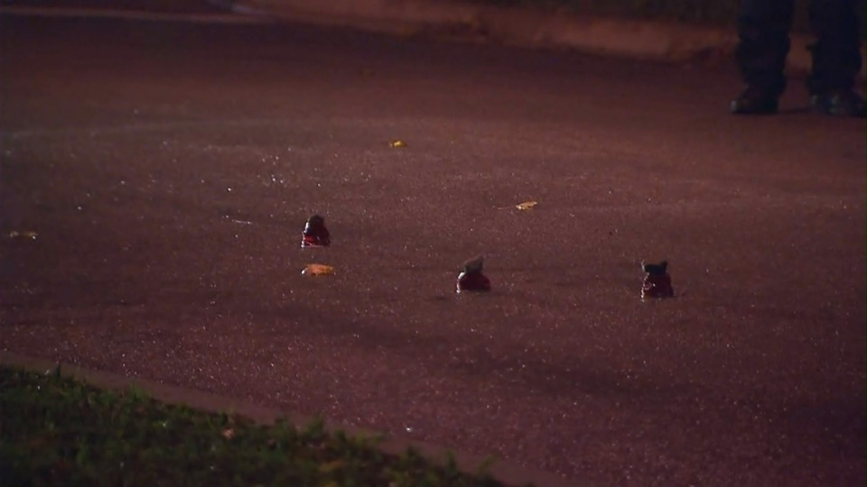 Evidence markers are seen on the ground following a shooting in Etobicoke that sent a man and a woman to hospital with life-threatening injuries on Tuesday, Oct. 18, 2016.