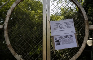 A closure notice and a bird flu news report from a Hindi newspaper are seen hanging at the entry gates of the Deer park in New Delhi, India, Friday, Oct. 21, 2016. City authorities have closed a sprawling park in the heart of New Delhi after eight birds died of suspected bird flu, days after the city zoo was closed to the public after nine birds died there. (AP Photo/Altaf Qadri)