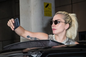 Singer Lady Gaga takes photographs as she leaves the BBC Broadcasting House after co-hosting the BBC Radio 1's breakfast show in London, Friday, Sept. 9, 2016. (Photo by Vianney Le Caer/Invision/AP)