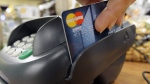 A customer swipes a MasterCard debit card through a machine while checking-out at a shop in Seattle on Nov. 2, 2009. (AP / Elaine Thompson)