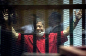 Former Egyptian President Mohammed Morsi, wearing a red jumpsuit that designates he has been sentenced to death, raises his hands inside a defendants cage in a makeshift courtroom at the national police academy, in an eastern suburb of Cairo, Egypt, Saturday, June 18, 2016. (AP Photo/Amr Nabil)