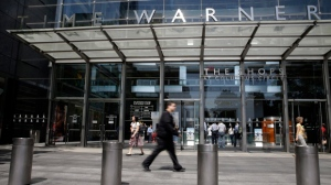 In this Tuesday, May 26, 2015 file photo, pedestrians walk by an entrance to the Time Warner Center in New York. On Saturday, Oct. 22, 2016, several reports citing unnamed sources said AT&T is in advanced talks to buy Time Warner, owner of the Warner Bros. movie studio as well as HBO and CNN. The giant phone company is said to be offering $80 billion or more, a massive deal that would shake up the media landscape. (AP Photo/Mary Altaffer)