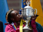 FILE - In this Monday, April 21, 2014 file photo, Rita Jeptoo, of Kenya, kisses the trophy after winning the women's division of the 118th Boston Marathon in Boston. As the world focuses on Russia and its doping scandal, running great and head of the Kenyan Olympic committee Kip Keino is preparing for the spotlight to turn to Kenya, and he is worried that his country could be facing a blanket ban from competition if it doesn't clean up its act. (AP Photo/Elise Amendola, File)