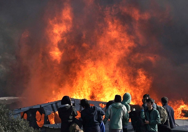 """Thick smoke and flames rise from amidst the tents after fires were started in the makeshift migrant camp known as """"the jungle"""" near Calais, northern France, Wednesday, Oct. 26, 2016. (AP Photo/Emilio Morenatti)"""