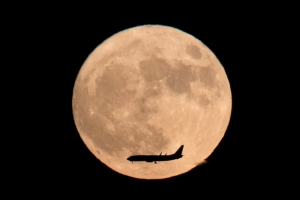 A jet plane flies across the moon seen from Beijing, China, Monday, Nov. 14, 2016. The brightest moon in almost 69 years will be lighting up the sky this week in a treat for star watchers around the globe. (AP Photo/Ng Han Guan)