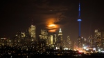 The full moon rises over the Toronto skyline in Toronto, Monday November 14, 2016. THE CANADIAN PRESS/Mark Blinch