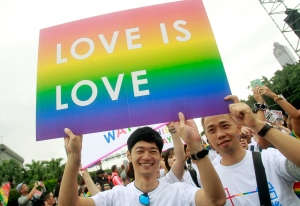FILE - In this Saturday, Oct. 31, 2015, file photo, revelers participate in a gay pride parade in Taipei, Taiwan. On Thursday, Nov. 17, 2016, Thousands of Taiwanese have protested outside the legislature for and against a bill that could make it the first place in Asia to legalize same-sex marriage. Organizers estimated that Thursday's protests attracted more than 20,000 people who carried placards, flew flags and chanted slogans as lawmakers deliberated the bill inside. (AP Photo/Chiang Ying-ying, File)