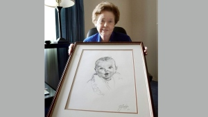 In this Feb. 4, 2004, file photo, Ann Taylor Cook, poses at her Tampa, Fla., home with a copy of her photo that is used on all Gerber baby food products. Gerber says Cook turned 90 on Sunday, Nov. 20, 2016. (AP Photo/Chris O'Meara, File)