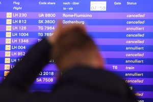 A passenger stands in front of the departure board at the airport in Frankfurt, Germany, Friday, Nov. 25, 2016. The Lufthansa pilots want to continue their strike at least until Saturday. (Arne Dedert/dpa via AP)