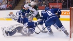 Toronto Maple Leafs goaltender Garrett Sparks blocks a shot as Minnesota Wild's Marco Scandella (6) and Maple Leafs' Matt Hunwick (2) look for the rebound during first period NHL hockey action in Toronto on Thursday March 3, 2016. THE CANADIAN PRESS/Chris Young