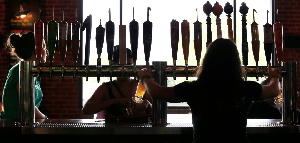 In this July 1, 2013 photo, a bartender pours two drafts from a selection of about 20 beverages on tap. (AP Photo/Charles Krupa)