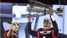 Ottawa Redblacks Henry Burris holds up the Grey Cup as Brad Sinopoli (88) looks on celebrating his team's win over the Calgary Stampeders in Toronto on Sunday, November 27, 2016. THE CANADIAN PRESS/Frank Gunn
