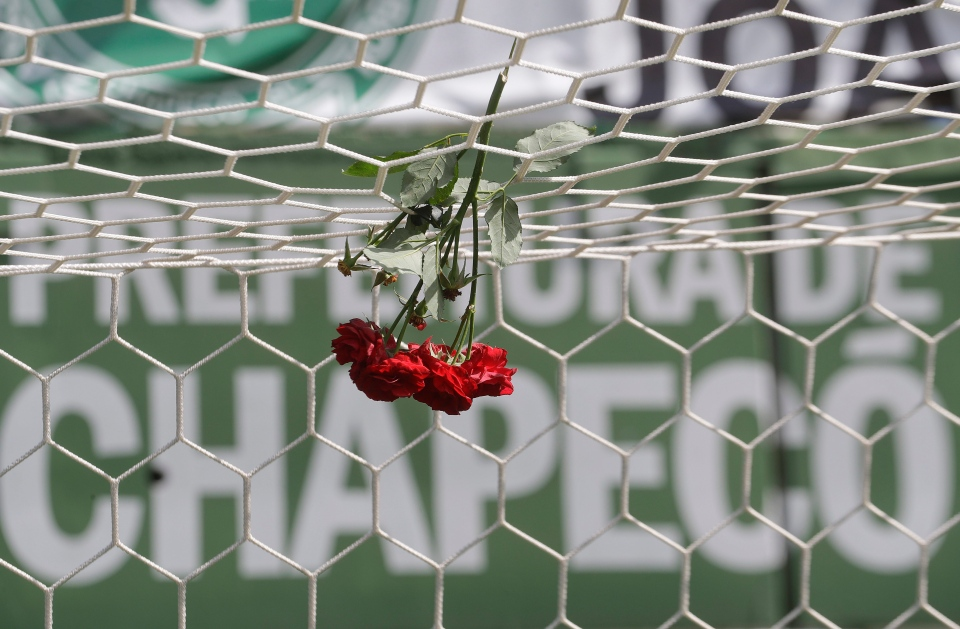 Flowers hang from a soccer net at the Arena Conda stadium in Chapeco, Brazil, on Tuesday, Nov. 29, 2016. (AP Photo/Andre Penner)