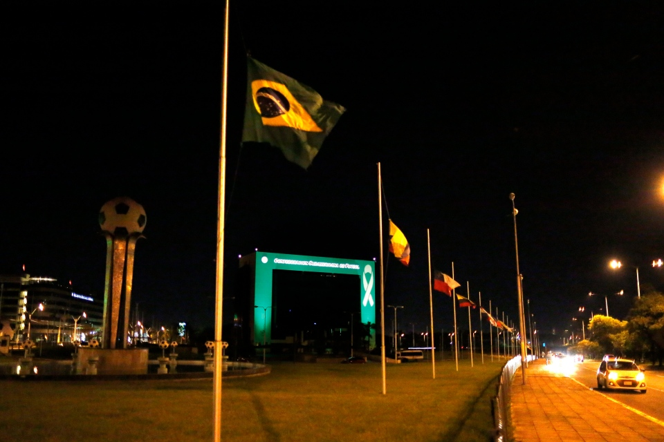 The headquarters of CONMEBOL, the South American Soccer Confederation, is illuminated in green and flags fly at half staff in memory of Brazil's Chapecoense's soccer players who died in a plane crash, in Asuncion, Paraguay, on Tuesday, Nov. 29, 2016. (AP Photo/Jorge Saenz)