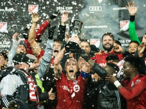 Toronto FC midfielder Michael Bradley (4) reacts with the trophy after defeating the Montreal Impact during extra time MLS eastern conference playoff soccer final action in Toronto on Wednesday, Nov. 30, 2016. (THE CANADIAN PRESS/Nathan Denette)