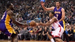 Toronto Raptors guard Kyle Lowry passes off the ball as he is double teamed by Los Angeles Lakers forwards Tarik Black (28) and Larry Nance Jr. (7) during first half NBA action in Toronto on Friday December 2, 2016. THE CANADIAN PRESS/Frank Gunn
