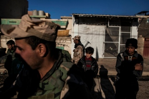 A group of Iraqi kids stand near some Iraqi Army soldiers near the frontline in Shyma district in Mosul, Iraq, Tuesday, Dec. 6, 2016. Iraqi forces, backed the U.S.-led international coalition, launched a campaign in October to retake Mosul, the country's second largest city and IS's last major urban bastion in Iraq. (AP Photo/Manu Brabo)