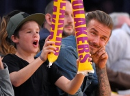 """FILE - This is a Sunday, April 3, 2016 file photo of former soccer player David Beckham, right, watches while his son, Cruz, bangs thunder sticks during the second half of an NBA basketball game between the Los Angeles Lakers and the Boston Celtics in Los Angeles. Cruz, has released his debut single, a holiday-themed pop track titled """"If Every Day Was Christmas."""" Beckham previewed the song Wednesday Dec. 7, 2016 on Britain's Capital FM.  (AP Photo/Mark J. Terrill, File)"""