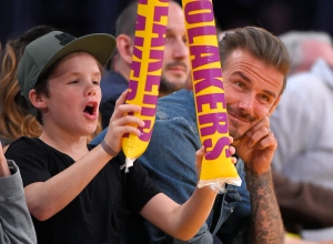 "FILE - This is a Sunday, April 3, 2016 file photo of former soccer player David Beckham, right, watches while his son, Cruz, bangs thunder sticks during the second half of an NBA basketball game between the Los Angeles Lakers and the Boston Celtics in Los Angeles. Cruz, has released his debut single, a holiday-themed pop track titled ""If Every Day Was Christmas."" Beckham previewed the song Wednesday Dec. 7, 2016 on Britain's Capital FM.  (AP Photo/Mark J. Terrill, File)"