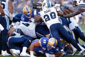 Winnipeg Blue Bombers quarterback Matt Nichols (15) makes the touchdown against Brandon Isaac (28) and the Toronto Argonauts during second half CFL action in Winnipeg, Saturday, September 17, 2016. THE CANADIAN PRESS/John Woods