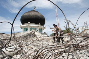 Police officers help clear rubble at the ruin of a mosque collapsed in Wednesday's earthquake in Tringgading, Aceh province, Indonesia, Saturday, Dec. 10, 2016. Tens of thousands people have been displaced by the powerful earthquake that hit Indonesia's Aceh province, authorities said Saturday, as the government and aid agencies pooled efforts to meet the basic survival needs of shaken communities. (AP Photo/Trisnadi)
