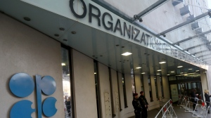 """Persons stand outside the headquarters of the Organization of the Petroleum Exporting Countries, OPEC, in Vienna, Austria, Saturday, Dec. 10, 2016. OPEC member states are meeting with Russia and other non-OPEC countries in Vienna for talks about a reduction in oil production. Secretary General Mohammed Barkindo said the discussions began Saturday in a """"positive atmosphere"""" at the headquarters of the oil producers' cartel. (AP Photo/Ronald Zak)"""