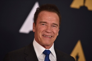 """In this Nov. 12, 2016 file photo, Arnold Schwarzenegger arrives at the 2016 Governors Awards in Los Angeles. Schwarzenegger, star of the new version of """"The New Celebrity Apprentice,"""" is unfazed that President-elect Donald Trump has retained a producer's stake in the show. Schwarzenegger said Friday, Dec. 9, 2016, that it's just business, comparable to his situation when he became California's governor and retained a screen credit and kept earning royalties for the """"Terminator"""" movie. (Photo by Jordan Strauss/Invision/AP, File)"""