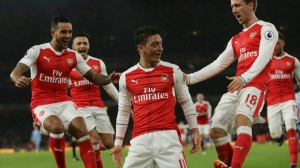 Arsenal's Mesut Ozil, centre, celebrates with his teammates after scoring a goal during the English Premier League soccer match between Arsenal and Stoke City at the Emirates stadium in London, Saturday Dec. 10, 2016. (AP Photo/Tim Ireland)