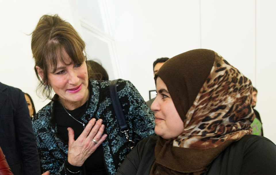 Quebec Immigration minister Kathleen Weil, left, talks with Syrian refugee Faten Nseirat during an event to mark the one year anniversary of the arrival of refugees from Syria to Canada, in Montreal, Sunday, December 11, 2016. THE CANADIAN PRESS/Graham Hughes