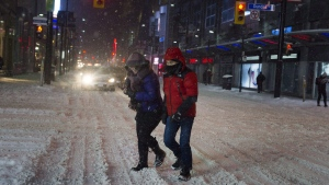 A couple is seen traversing the Yonge and Dundas intersection during a snow storm in Toronto in a March 1, 2016, file photo. (THE CANADIAN PRESS/Christopher Katsarov)