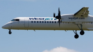 A WestJet Airlines Encore Bombardier Q400 regional jetliner lands in Calgary, Alberta on July 19, 2016. THE CANADIAN PRESS IMAGES/Larry MacDougal