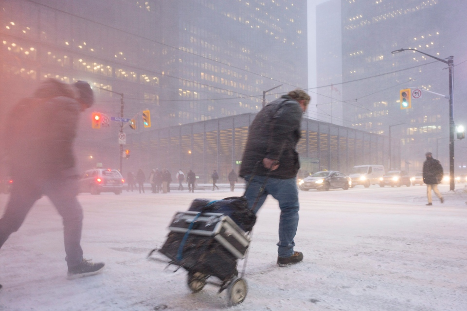 A person makes their way across King Street as snow flies through the air during a squall in downtown Toronto's financial district, on Thursday, Dec. 15, 2016. (The Canadian Press/Graeme Roy)