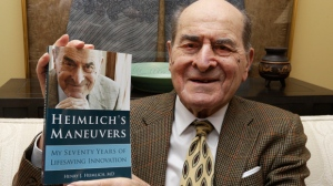 In this Feb. 5, 2014, file photo, Dr. Henry Heimlich holds his memoir prior to being interviewed at his home in Cincinnati. Heimlich, the surgeon who created the life-saving Heimlich maneuver for choking victims has died Saturday, Dec. 17, 2016, at Christ Hospital in Cincinnati. He was 96. (AP Photo/Al Behrman, File)