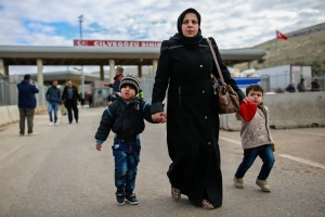 Iptisam Muhammed, 25, from Aleppo, Syria, walks with her children, names not given, after crossing into Turkey at the Cilvegozu border gate with Syria, near Hatay, southeastern Turkey, Sunday, Dec. 18, 2016. (AP Photo/Emrah Gurel)