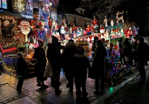 In this Dec. 14, 2016, photo, visitors to the Dyker Heights neighborhood of the Brooklyn Borough of New York gather in front of Lucy Spata's house, as they tour the area known for it's elaborate and over-the-top Christmas displays. (AP Photo/Kathy Willens)