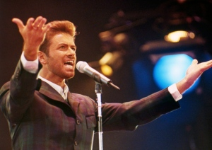 "In this Dec. 2, 1993 file photo, George Michael performs at ""Concert of Hope"" to mark World AIDS Day at London's Wembley Arena. According to a publicist on Sunday, Dec. 25, 2016, the singer has died at the age of 53. (AP Photo/Gill Allen)"