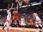 Houston Rockets guard James Harden (13) scores as Toronto Raptors guard DeMar DeRozan (10) defends and guard Kyle Lowry (7) and forward Patrick Patterson (54) look on during second half NBA basketball action in Toronto on Sunday, January 8, 2017. THE CANADIAN PRESS/Frank Gunn