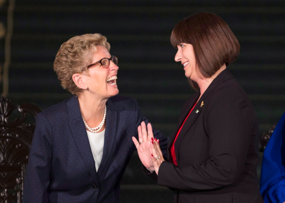Ontario Premier Kathleen Wynne laughs with Marie-France Lalonde, Minister of Government and Consumer Services and Minister Responsible for Francophone Affairs after her swearing in at Queen's Park in Toronto on Monday, June 13, 2016. THE CANADIAN PRESS/Peter Power