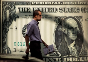 In this Thursday, Nov. 3, 2016, file photo, a man walks past a poster showing a U.S. dollar outside an exchange office in Cairo. (AP Photo/Amr Nabil, File)