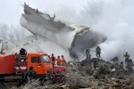 Kyrgyz Emergency Ministry officials and firefighters work among remains of a crashed Turkish Boeing 747 cargo plane at a residential area outside Bishkek, Kyrgyzstan Monday, Jan. 16, 2017. The cargo plane crashed Monday morning, killing people in the residential area adjacent to the Manas airport as well as those on the plane. (AP Photo/Vladimir Voronin)
