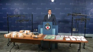 Police seized multiple firearms, drugs and cash from Toronto homes on Sunday.