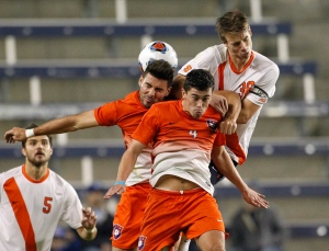 Clemson's Kyle Murphy, left, Oliver Shannon, center, and Syracuse's Oyvind Alseth, right, go up for the ball as Syracuse defender Louis Cross (5) looks on in the second half of an NCAA College Cup soccer match on Friday, Dec. 11, 2015, in Kansas City, Kan. (AP Photo/Colin E. Braley)