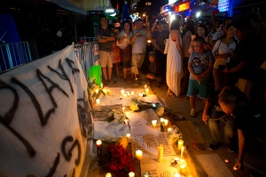 Local residents gather to place candles and banners calling for peace and unity in Playa, outside the Blue Parrot club where several people were killed in early morning gunfire, in Playa del Carmen, Mexico, on Monday, Jan. 16, 2017. (AP Photo/Rebecca Blackwell)