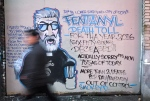 A man walks past a mural by street artist Smokey D. about the fentanyl and opioid overdose crisis in the Downtown Eastside of Vancouver, B.C., on Thursday, Dec. 22, 2016. (The Canadian Press/Darryl Dyck)