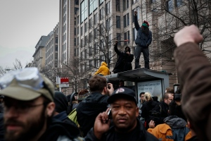 Protesters raise their fists atop of a bus shelter during a demonstration after the inauguration of President Donald Trump on Friday, Jan. 20, 2017, in Washington. (AP Photo/John Minchillo)