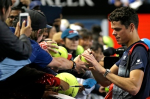 Canada's Milos Raonic signs autographs after defeating France's Gilles Simon during their third round match at the Australian Open tennis championships in Melbourne, Australia, Saturday, Jan. 21, 2017. (AP Photo/Aaron Favila)
