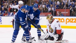 Ottawa Senators goalie Mike Condon (1) makes a save in front of Toronto Maple Leafs' Zach Hyman (11) and Frederik Gauthier (33) during second period NHL hockey action, in Toronto on Saturday, January 21, 2017. THE CANADIAN PRESS/Chris Young