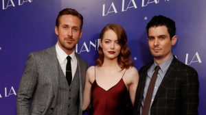 Actors from left, Ryan Gosling and Emma Stone pose for photographers with director Damien Chazelle upon arrival at the screening of the film 'La La Land' in London, Thursday, Jan. 12, 2017. (Photo by Joel Ryan/Invision/AP)