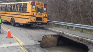 A massive sinkhole is pictured near a school bus in the Symes Road and Hillborn Avenue area Tuesday January 24, 2017.  (Cam Woolley /CP24)