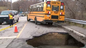A massive sinkhole is pictured near a school bus in the Symes Road and Hillborn Avenue area Tuesday January 24, 2017.